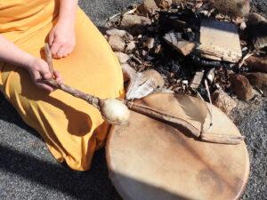 kvinna med orange klänning slår på en trumma