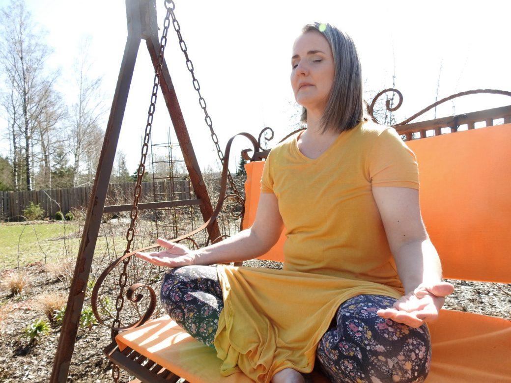 Annika i orange klänning sitter i en hammock